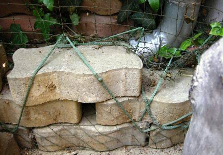 Sicherung des Netzes am Boden mit Steinen